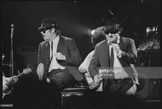 Dan Aykroyd and John Belushi performing on stage as the Blues Brothers.