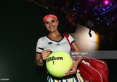 Sania Mirza of India signs a tennis ball after partnering Martina Hingis of Switzerland in their doubles match against Hao-Ching Chan and Yung-Jan Chan of Republic of China during day 6 of the BNP Paribas WTA Finals Singapore at Singapore Sports Hub on October 28, 2016 in Singapore.