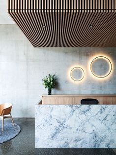 The reception's graceful composition of white marble, timber battening, oak veneer and jewel-like wall lights provides a striking first impression.