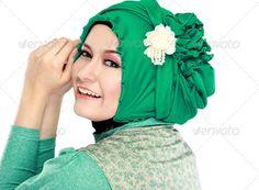Young beautiful muslim woman with green costume wearing hijab - Stock Photo…