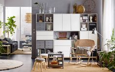 Grey living room with rattan rocking chair and woven rug in front of grey and white open and closed storage.