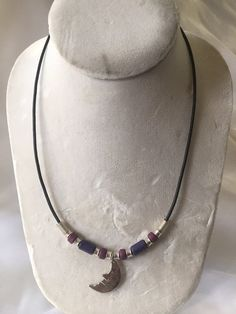 This 18 inch, one of a kind, unisex leather cord necklace features purple and plum colored clay beads, nickle free, silver plated beads, toggle clasp and man in the moon charm on a black leather cord. This necklace would be a great gift for any moon lover!    This item is ready for immediate shipment, so you will receive this exact item. | Shop this product here: spreesy.com/sterling_dreams/10 | Shop all of our products at http://spreesy.com/sterling_dreams    | Pinterest selling powered by…