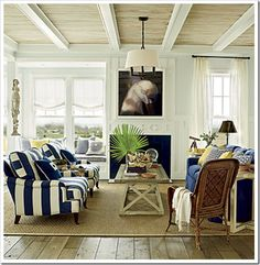 Beachy board and batten living room with blue walls and navy and white accents.