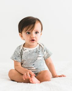 Sweet baby boy in cute little romper with adorable high seas illustration. For your little pirate hipster babe. Simple blue print on white short sleeve romper perfect for spring. Made from organic cotton so it's soft on baby's sensitive skin. From Noble Carriage's Winter Water Factory collection. PHOTOGRAPHY BY: http://studiocastillero.com/