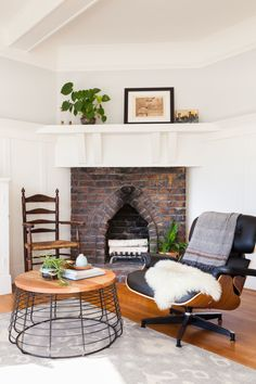 The fireplace was also original to the space, but the client brought in the Eames lounger, antique armchair, and CB2 coffee table.