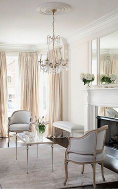 Pale neutral formal sitting room with silver accents, an oversized triptych mirror, crystal chandelier and dramatic floor-to-ceiling cream silk curtains.