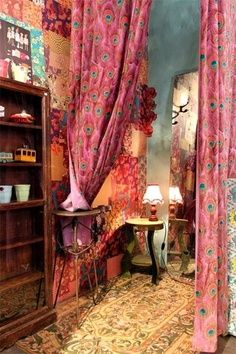 I like the idea of partially separating spaces with artfully draped curtains... BTW, this pink peacock fabric is available at JoAnn's Fabrics & crafts