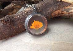 Szklany wisiorek z żółtym kwiatem.