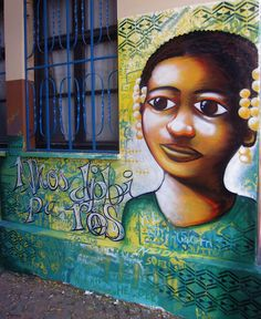 """Another piece in the same school. The patterns, called """"pano de terra,"""" are well-known in Cape Verde. The words next to the child are in creole (kriolu) and mean """"look at us,"""" """"pay attention to us,"""" and """"help us"""" all in one phrase."""