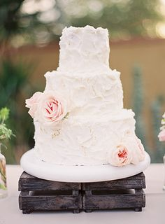 Choose a classic and traditional wedding cake; Beautiful frosting with a couple lovely blooms to adorn it. Bright white and blush pinks on a rustic stand couldn't be more appealing!  http://www.sterlingweddingsandevents.com/  #sterlingweddingsandevents #weddingcake #cake #arizona #arizonaweddings  Photo Credit: Brushfire Photography