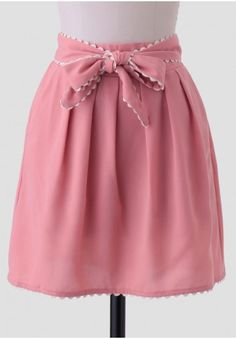 <p>Create a romantic ensemble with this dusty pink skirt accented with scalloped trim at the hems and a self-tie sash. Finished with side pockets, pleats at the front, and a partially elasticized waistband, this charming skirt looks adorable styled with a neutral button-up blouse and T-strap heels. Fully lined.</p> <p>100% Polyester<br /> Imported<br /> 25
