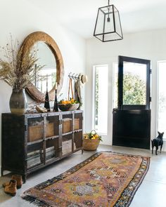 White painted floors, black Dutch door, vintage console, and warm russet tones. Design by Heather Bullard. Door Entryway, Entryway Tables, Everything But The House, Half Doors, House Made, Cool Chairs, Sweet Home, House Design, Foyer Design