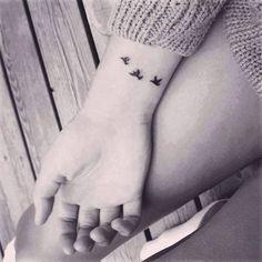 Little wrist tattoo of three birds flying.