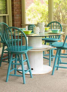 table en touret blanche avec un plateau en verre, chaises en bois bleus, tapis gris, amenagement terrasse