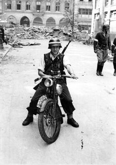 A young Warsaw fighter rides a German motorbike, carries a German rifle, and wears a German helmet and boots. August 1944.