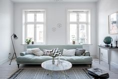 ultra light blue sofa with lower base multicolored throw pillows round glass top coffee table white walls with glass windows whitewashed wood siding floors Mint Living Rooms, Narrow Living Room, Living Room Green, Living Room Sofa, Home Living Room, Living Room Designs, Living Room Decor, Small Living, Dining Room
