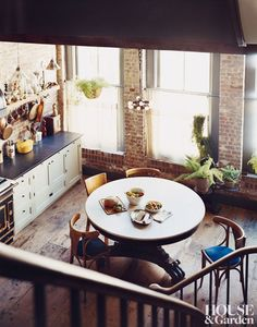 This dark, cozy Manhattan home belonging to Carter Smith. loft apartment, kitchen, exposed brick wall, white painted cabinets, loft living, urban living, city living, NYC loft