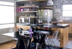 A bancada de concreto, com pintura de epóxi preto, e as prateleiras suspensas por cabos de aço dividem os espaços sem fechá-los. Maíra Acayaba / Casa e Jardim