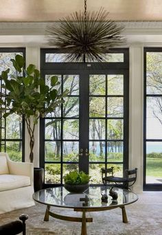 Gorgeous French doors and windows with black trim make a striking statement in this space. Kara Mann Design
