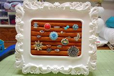 Ring-holder: Rolled felt, glued to cardboard, in a pretty picture frame. I'd do it with velvet instead.