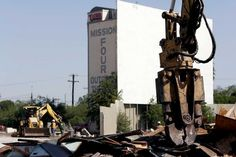 Demolition crews tear down he outlying bricks and fence along the old Mission Drive-In on May 18, 2009, to prepare the property for construction of a new library, office and retail space. The marquee screen in the background however will be preserved and incorporated into the 26 acre re-developed site as an amphitheater.