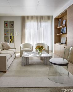 The modern, simple living room in this Palm Beach home is all about a calming, neutral color palette. The sand colored sofa is covered in a Great Plains fabric, and the cream colored armchairs are by Jonas. The glass chair is by Jacques Adnet and René Coulon, and the concrete wall plaques are by Radu Comsa.