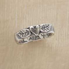 """STERLING HEART GROWS FONDER RING -- Jes MaHarry plants a heart amid sterling silver leaves; a symbol of ever-growing love. Hand-hammered band inscribed with """"love always."""" USA. Exclusive. Whole and half sizes 5 to 10. Tapers 1/8"""" to 3/16""""W."""