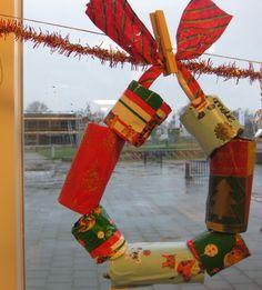 Kerstkrans gemaakt van hele en halve toiletrolletjes, beplakt met mooi cadeaupapier