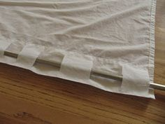 The Wicker House: $5 Curtains. Cut slits in 1 layer of the top hem of the sheet to use as the curtain tabs.