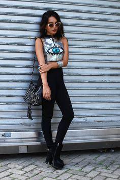 Alana Ruas silver evil eye crop top worn with high-waisted black denim and cat-eye sunglasses