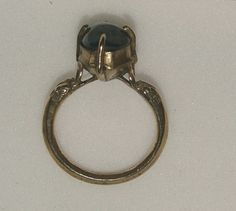 Italy, Venice 13th/14th century Silver ring, the hoop terminating in a pair of dragon's heads supporting a transverse octagonal bezel with four claws set with a cabochon sapphire.