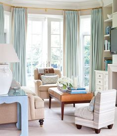 Whisper-Soft Living Room Palette      A calm and serene setting for a young family.    Floor-to-ceiling watery blue drapes hung on a brass rod add opulence to comfortable pieces, such as a caramel leather ottoman.