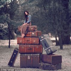 Packing light: A model sits on top of some enlarged vintage luggage