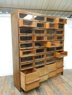 An oak haberdashery cabinet. Thirty two glazed drawers over four large deep drawers, bronze drawer pulls and card holders. Very good original condition. English 1930's.