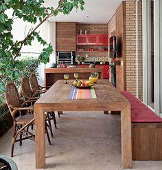 Ao desenhar a varanda gourmet, a designer de interiores Marina Linhares deixou o espaço com cara de área externa. Daí a escolha de materiais rústicos como cimento queimado, madeira e tijolos.