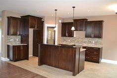 Stunning kitchen with glass backsplash, under cabinet lighting, center island, granite countertops, walk-in pantry & more!