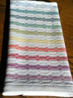 Handwoven kitchen towel designed and woven with a traditional Swedish hand weaving pattern of crisp rainbow stripes alternating with white