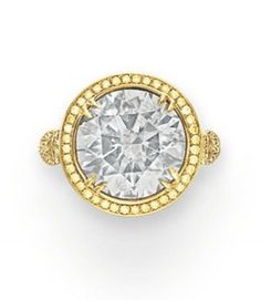 A COLORED DIAMOND RING   Set with a circular-cut fancy greenish gray diamond, weighing approximately 8.48 carats, in a backed yellow gold setting, within a circular-cut yellow diamond surround, to the circular-cut diamond bifurcated shoulders and half hoop, mounted in 18k gold and platinum