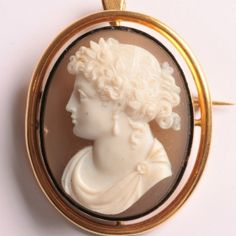 Hardstone cameo brooch of a woman in profile to the left, white on grey background.  The brooch can also be worn as a pendant by using the hinged loop.  Small chip to the left-hand base.  41 x 50mm  €2350  www.Osprey.fr Gray Background, Vintage Jewelry, Profile, Paris, Jewels, Woman, Antiques, Pendant, Grey