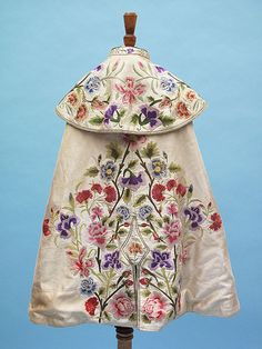 A late 19th century cream cape with heavy floral embroidery done by hand and a mauve silk lining.