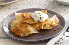 Shortcut Pierogies recipe  2 cups  cooled mashed potatoes  1/2 cup  (1/2 of 8-oz. tub) PHILADELPHIA Chive & Onion Cream Cheese Spread  1/4 tsp.  pepper  36  won ton wrappers  1  egg white, lightly beaten  3 Tbsp.  butter, divided  1/2 cup  BREAKSTONE'S or KNUDSEN Sour Cream