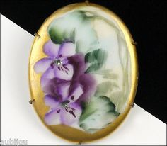 Description: Vintage oval hand painted floral motif porcelain brooch; decorated with purple violets and greenery; burnished gold border; brass setting. Designer/Makers Marks, Hallmarks, Tags: Unsigned