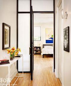 """进门的玄关区域,正对的是十分少见的卧室空间,而隐蔽的卧室空间,自然要想办法进行""""保护"""",带有门的毛玻璃隔断,有效的将2个区域分开,同时也起到了双层防护的作用。"""