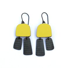 Colourful earrings in a minimalist style combining bright yellow laminate with stripy oxidised silver drops. A light grey laminate is used on the reverse. Size: approx. 55mm (L) x 18mm (W) x 4mm (D) Also available in teal, red, orange, white, light grey, dark grey, and black.