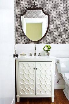 Stunning bathroom with Quadrille China Seas Edo wallpaper - Black/White, circles door single bathroom vanity with marble countertop, subway tiles backsplash and glossy black mirror.