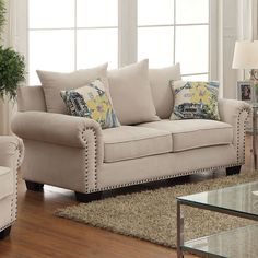 A sophisticated addition to any home, this chic loveseat provides a comforting seating area with its multitude of pillows. Gorgeous nailhead trim adorns the rolled arms and showcase the structured framework beautifully.