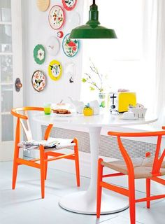 Charming Orange Chairs Dining in front of window.  Sweet Plate Display on Wall.  Vintage Green Industrial Light.