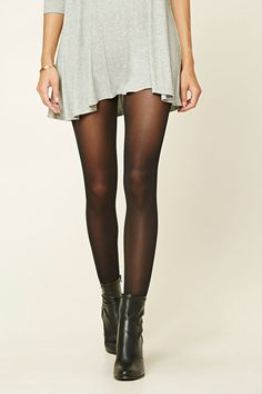 A pair of opaque tights featuring a solid design and an elasticized waist.