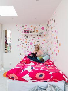 chambre ado fille blanche avec une déco murale en pois multicolores et une literie à grosses fleurs rose vif