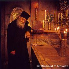 Greek Orthodox priest inside of the tomb of Christ, Holy Sepulcher Church, Jerusalem.